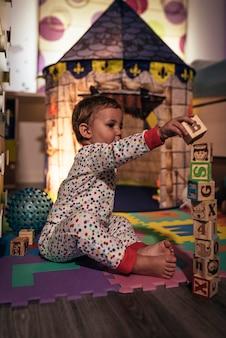 집에서 블록 장난감을 가진 작은 소년. 어린 시절 개념.