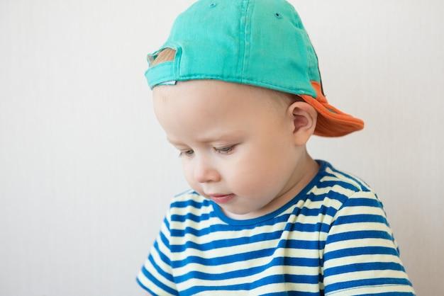 Маленький мальчик с голубыми глазами в полосатой футболке и кепке портрет