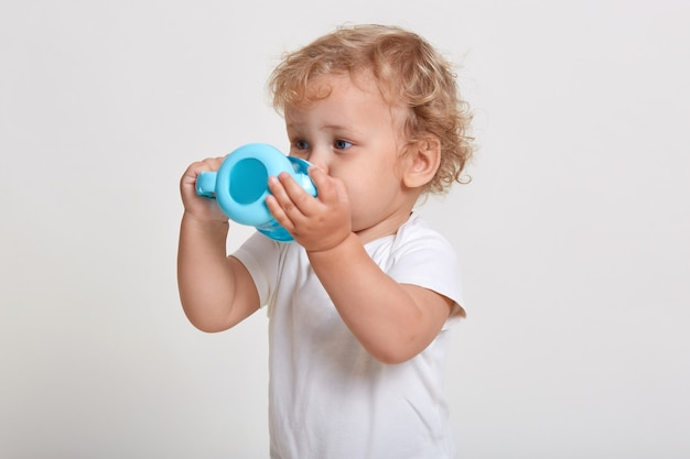 Little boy with blue plastic baby cup drinking water, thirsty child in t shirt posing isolated over white space
