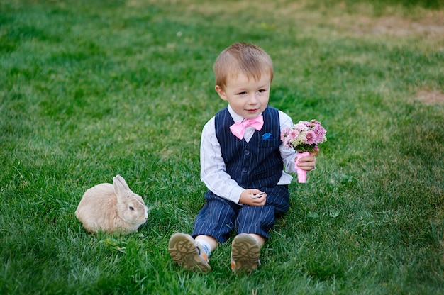 Little boy with a bouquet of flowers and a rabbit sitting on the grass