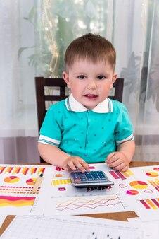 Маленький мальчик с бизнес-графиками и калькулятором в качестве аналитика