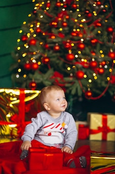 Little boy with christmas gifts by chriostmas tree