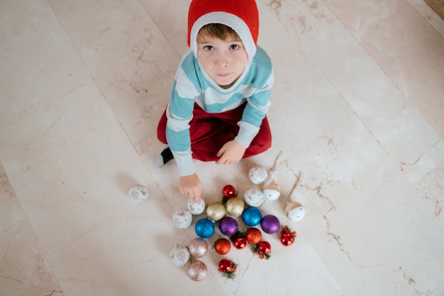 Little boy with christmas ornaments
