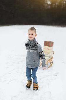 Маленький мальчик с коробками для рождественских подарков на деревянных санках в снегу