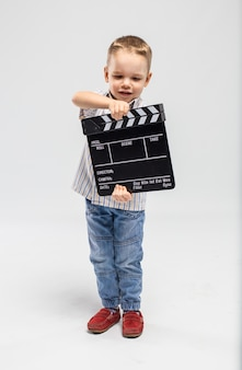 Little boy with clapper board at studio