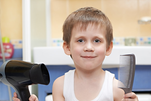 Little boy with a comb and hair dryer