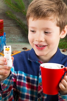 Little boy with a cup of hot chocolate with marshmallows and snowman on the background of gifts, christmas tree and christmas decorations