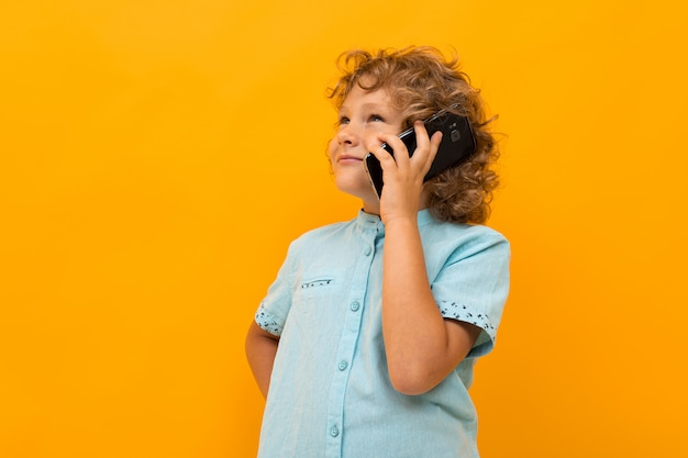 Little boy with curly hair in blue shirt and shorts calls the phone isolated on yellow background