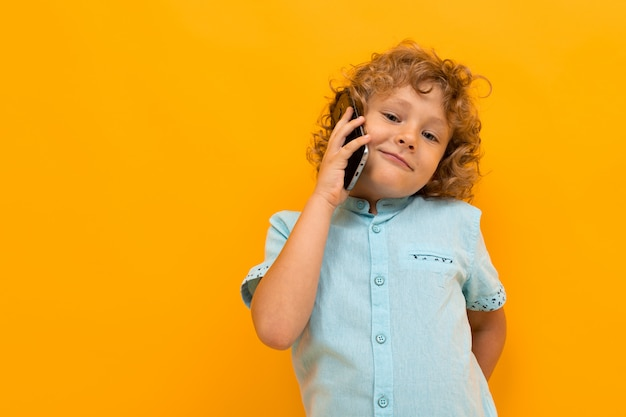 Little boy with curly hair in blue shirt and shorts calls the phone isolated on yellow