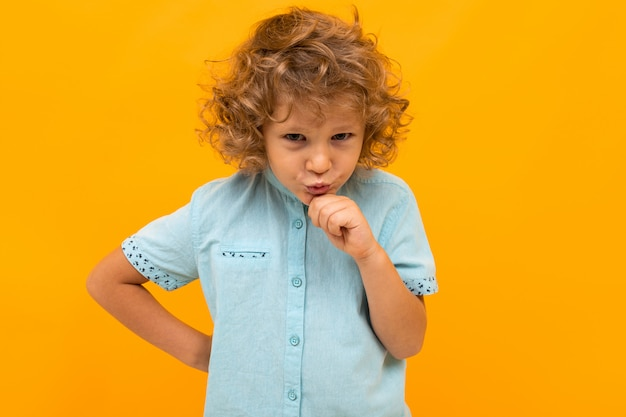 Little boy with curly hair in blue shirt and shorts is shoked isolated on yellow background