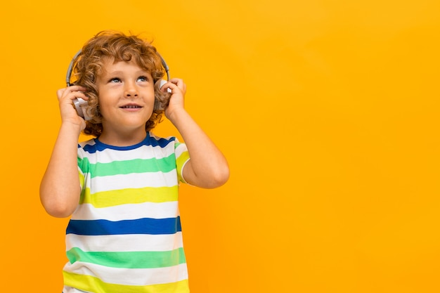 Little boy with curly hair in colourful t-shirt and shorts listen to music with big earphones isolated on yellow