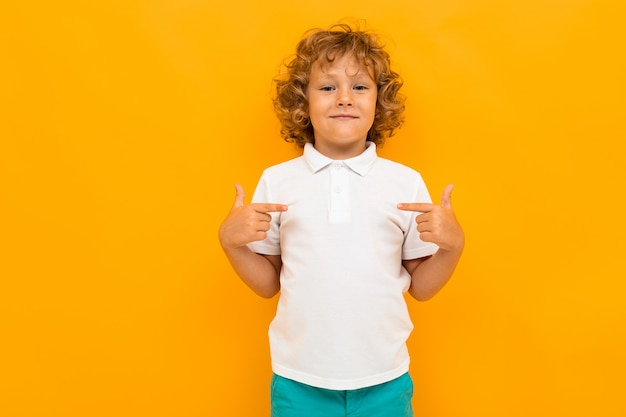 Little boy with curly hair in colourful t-shirt and shorts shows thumbs for himself isolated on yellow background