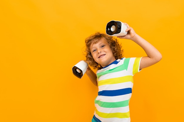 Маленький мальчик с вьющимися волосами в красочной футболке и шортах держит маленькие музыкальные колонки и танцы, изолированных на желтом фоне
