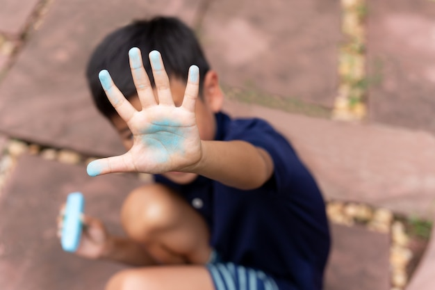 Little boy with dirty hand of blue chalk