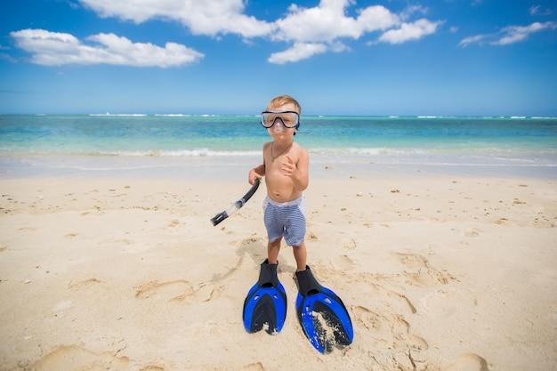 ダイビングマスクとフィンを持った少年がビーチで泳ぎに行く