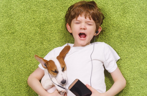Little boy with a dog listen to music.