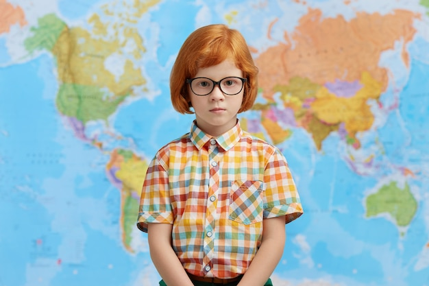Little boy with ginger hair, wearing checkered shirt and eyeglasses, standing against map, going to school. clever pupil standing in cabinet of geography at school, going to have lesson
