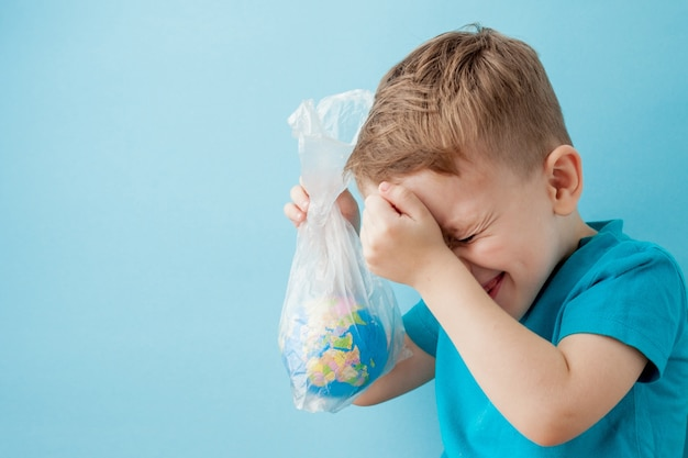 Little boy with a globe in a package on a blue background.