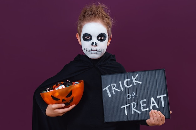 Little boy with halloween makeup and skeleton costume are holding sweets and blackboard with the text: trick or treat. halloween concept.