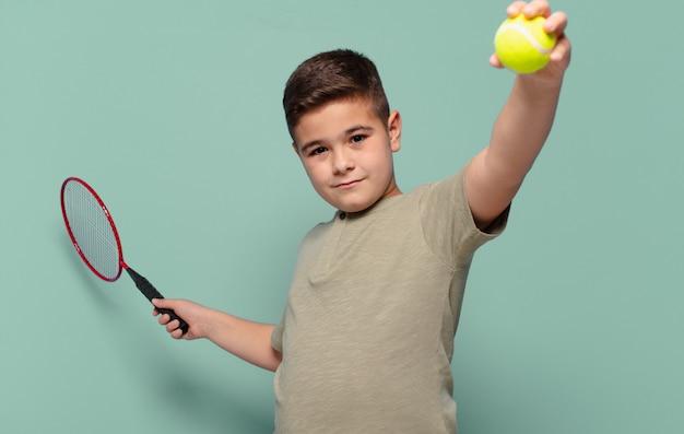 幸せな表現のテニスのコンセプトを持つ小さな男の子