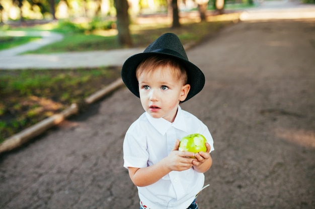 Little boy with a hat on his head in the park eating an apple