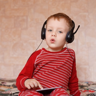 Little boy with headphones listening to music and singing