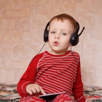 Маленький мальчик в наушниках, слушает музыку и поет