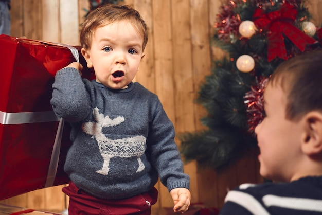 Little boy with his christmas present staring at the camera while his brother stares at him