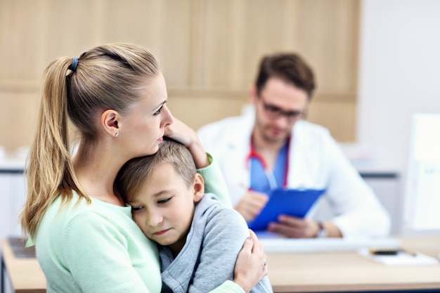 Little boy with his mother in clinic being examined by pediatrician