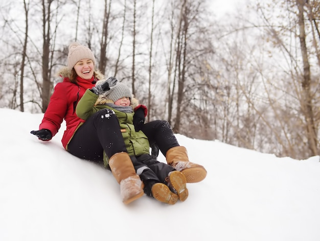Little boy with his mother enjoy riding on ice slide in winter