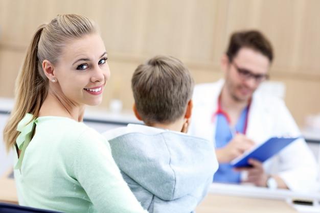 小児科医によって検査されているクリニックで彼の母親と一緒に小さな男の子