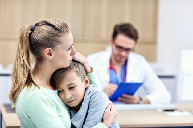 소아과 의사가 검사하는 병원에서 그의 어머니와 어린 소년