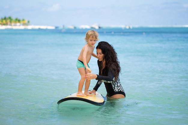 서핑을 배우는 그의 어머니와 함께 작은 소년