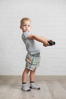 Little boy with joystick looking at camera