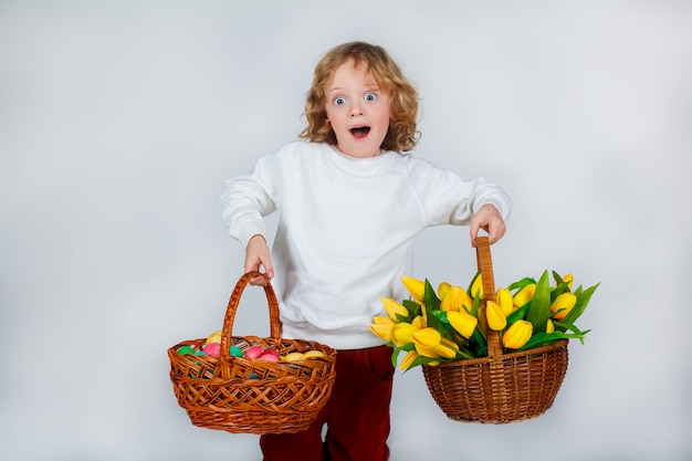 Little boy with long blond curly hair holds in his hands baskets with tulips and easter eggs . spring holidays concept.