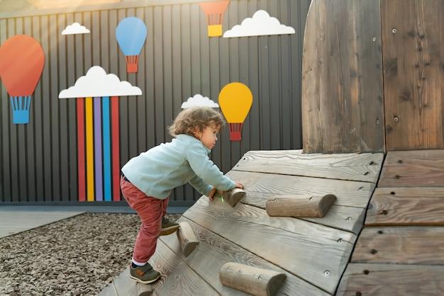 야외 공공 놀이터에서 나무 미끄럼틀을 등반하는 긴 머리를 가진 어린 소년