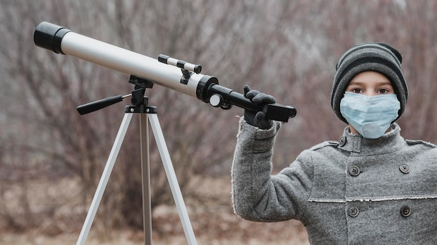 망원경을 사용 하여 의료 마스크와 어린 소년