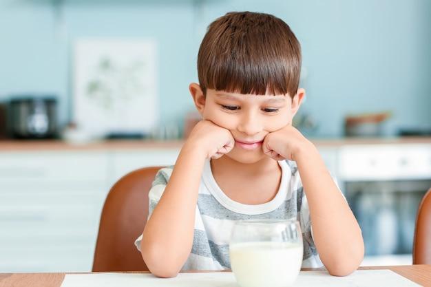 Little boy with milk in kitchen