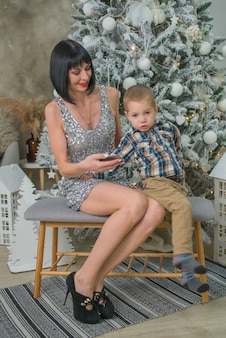 Little boy with mom at home near the christmas tree with gifts in christmas