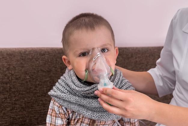 彼の顔にネブライザーマスクを持つ小さな男の子