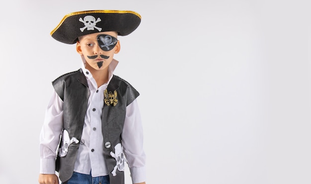 A little boy with a pensive look in a pirate costume with makeup on his face. isolated white wall.