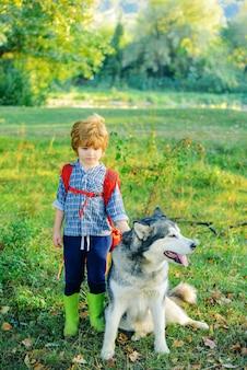 自然の休暇のキャンプの観光と犬との休暇の概念の子供たちを探検するペットの犬と一緒の小さな男の子...