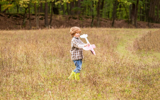 Маленький мальчик с самолетом. маленький ребенок мечтает стать летчиком. ребенок играет с игрушечным самолетом. счастливый ребенок играет. счастливый ребенок, играя на открытом воздухе. счастливый мальчик играть в самолет.