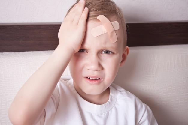 頭の上に石膏を持つ少年と気分が悪い。