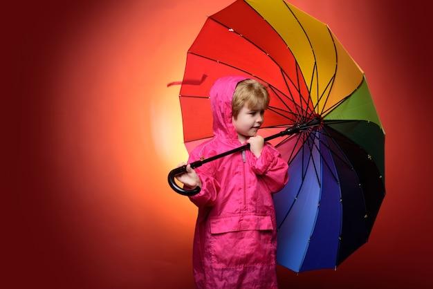 빨간색 배경에 고립 된 무지개 색 우산을 가진 어린 소년. 어린이는 귀하의 제품과 서비스를 광고합니다. 가을 비 날에 가을 옷을 입고 귀여운 작은 아이 소년. 비에 아이입니다.