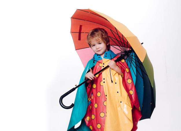 白い背景で隔離の虹色の傘を持つ少年。秋のコレクション全体のセール、信じられないほどの割引と素晴らしい選択。かわいい男の子は秋の準備をしています。