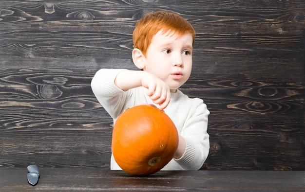 赤い髪の少年はカボチャを切る場所を見つけ、ハロウィーンを祝う準備をし、ランプを準備します