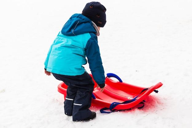 雪の中で赤いそりを持つ小さな男の子