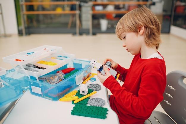 Маленький мальчик с роботом-конструктором, собирающим техническую игрушку, детская робототехника, конструктор, робот