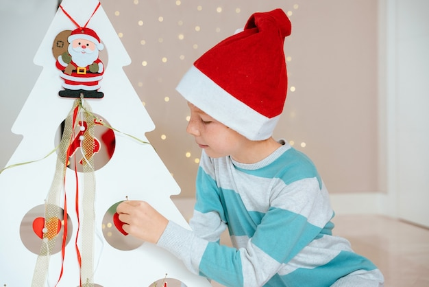 Little boy with santa claus next decorated tree